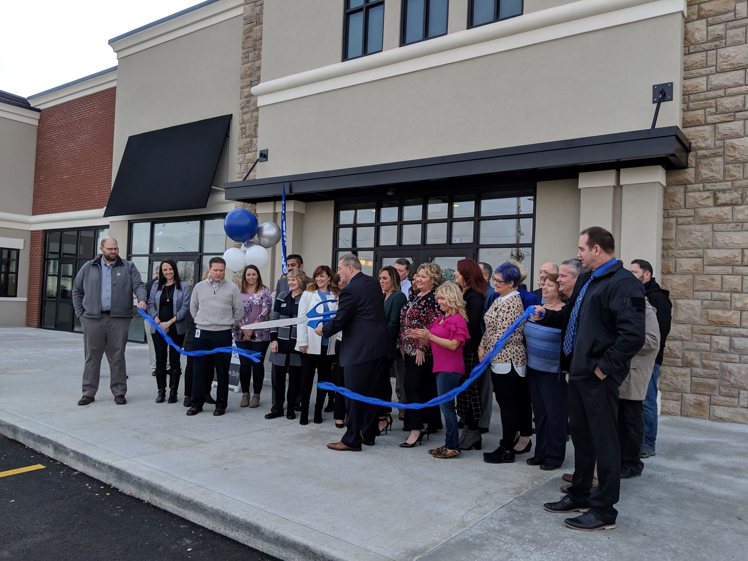 Picture of a crowd of people standing outside a stone building and cutting a blue ribbon as the ribb