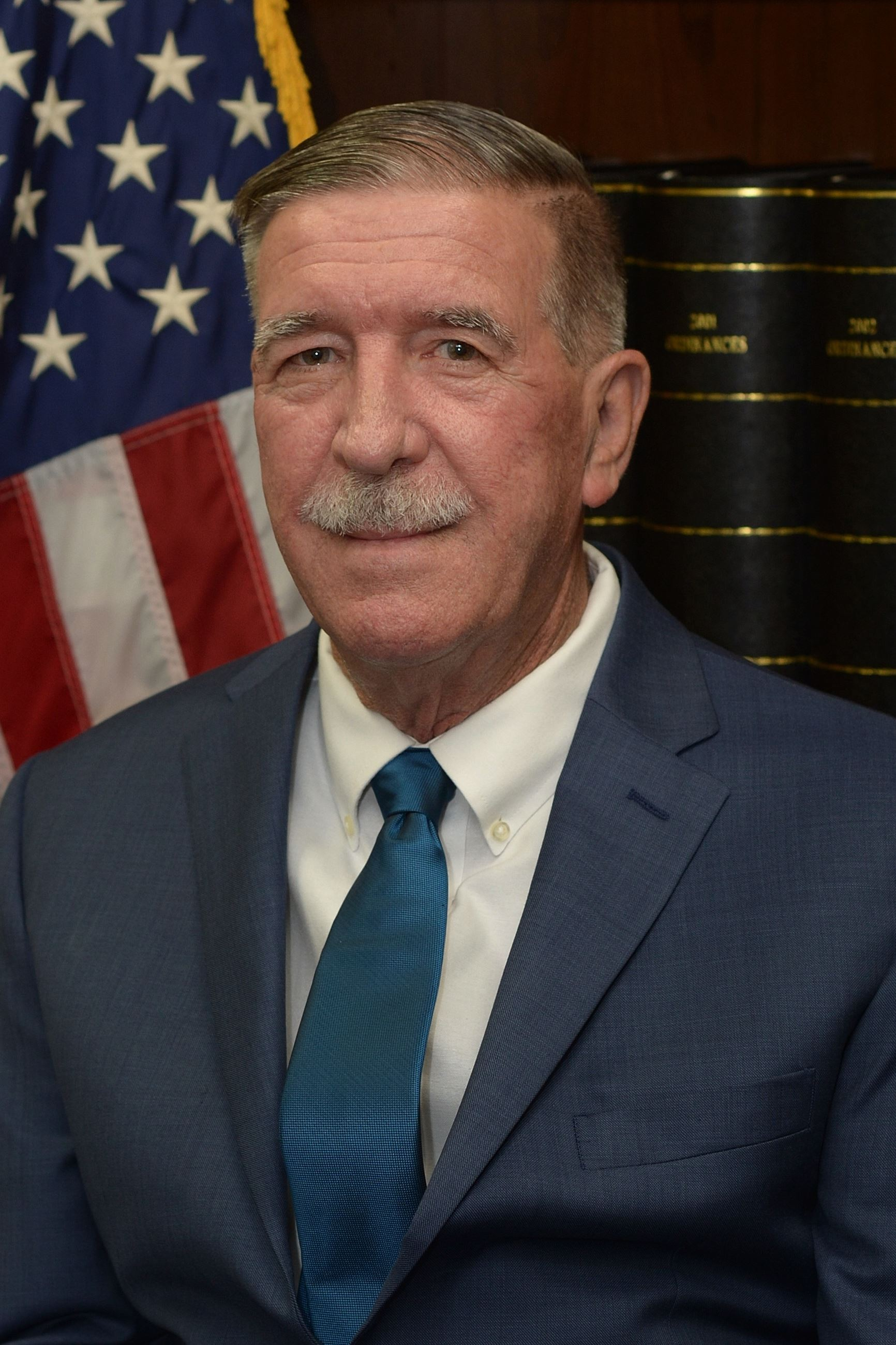 Headshot of a man with grey hair wearing a suit in front of an American flag and law books